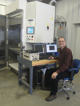 Gary Delserro sits at his lab's Highly Accelerated Life Test (HALT) Chamber, which performs combined temperature and vibration loads simultaneously.