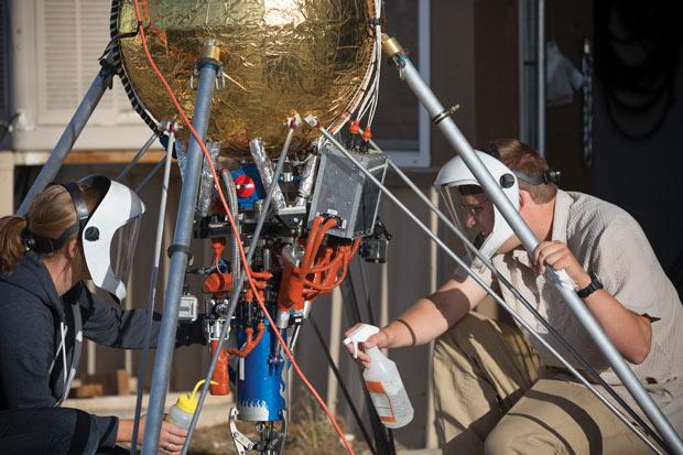 Masten rocketeers Ellen Moyer and Wyatt Rehder prep Masten's Xodiac rocket for flight.  Image courtesy of Chad Slattery.