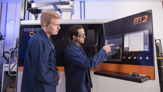 Sintavia applications engineer Shawn Morgan (left) and additive technician Juan Manjarres (right), work with one of the metal additive manufacturing company's newest machines, an M2 cusing from Concept Laser.