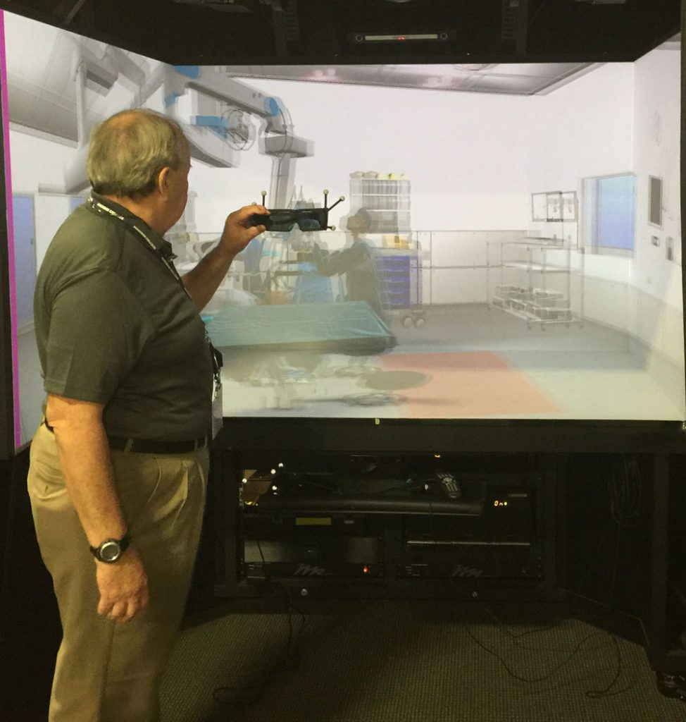 Rave Cave President Art Adlam prepares for virtual surgery in front of a more portable, but less immersive VR CAVE.