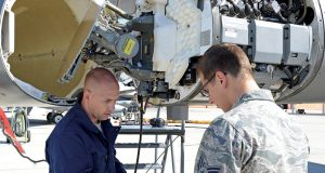 Two members of the U.S. Air Force do pressurization maintenance on an F-16 Fighting Falcon radar waveguide. Such maintenance is now done based on pre-established rules such as hours of use, but newer aircraft are being delivered with the capability to self-report maintenance needs using sophisticated IoT-based sensors. Image courtesy of the U.S. Air Force; Kenji Thuloweit, photographer.