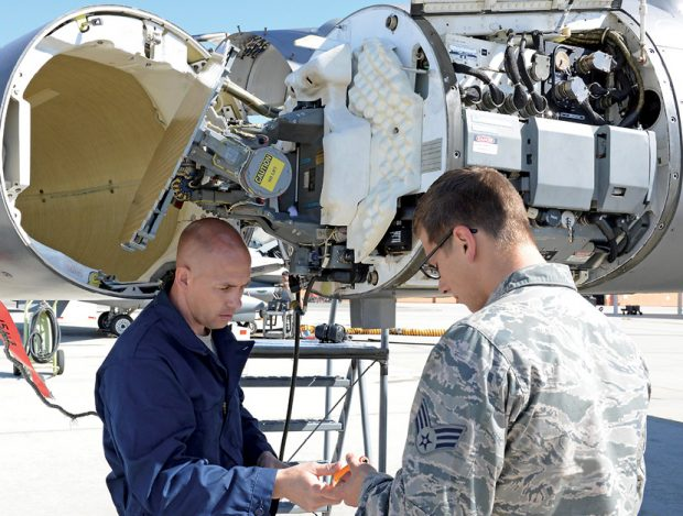 Two members of the U.S. Air Force do pressurization maintenance on an F-16 Fighting Falcon radar waveguide. Such maintenance is now done based on pre-established rules such as hours of use, but thanks to digitalization, newer aircraft are being delivered with the capability to self-report maintenance needs using sophisticated IoT-based sensors. Image courtesy of the U.S. Air Force; Kenji Thuloweit, photographer.